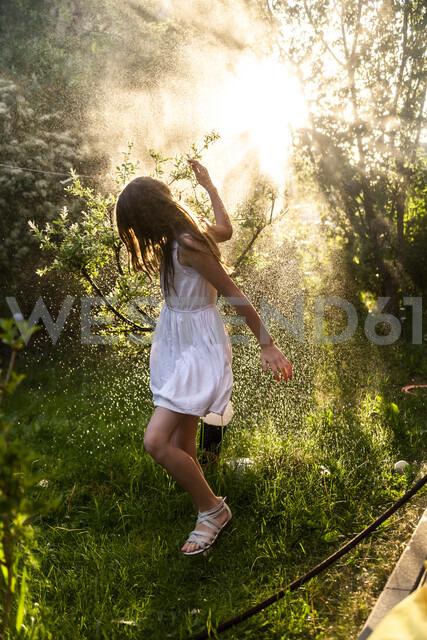 Girl having fun with garden hose in summer - SARF03733