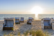 Germany, Schleswig-Holstein, Sylt, beach and empty hooded beach chairs at sunset - EGBF00247