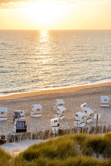Germany, Schleswig-Holstein, Sylt, beach and empty hooded beach chairs at sunset - EGBF00250
