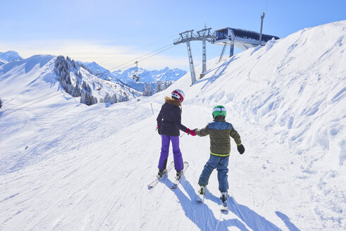 Rear view of girl and brother holding hands on ski slope, Gstaad, Switzerland - CUF04755