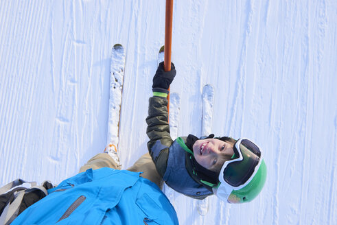 Overhead portrait of boy skier looking up at father, Gstaad, Switzerland - CUF04758