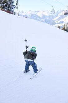 Rear view of boy skiing down ski slope, Gstaad, Switzerland - CUF04761