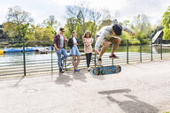 Young male skateboarder doing jump trick for friends in Battersea Park - CUF04836