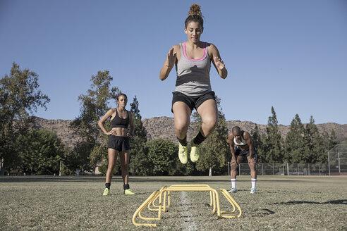 Woman jumping over agility hurdles - ISF01152