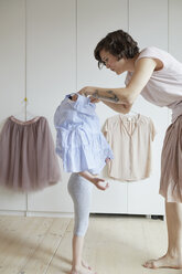 Mother helping daughter to dress - ISF01260
