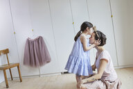 Mother and daughter in bedroom, face to face, daughter kissing mother on head - ISF01263