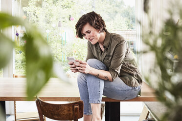 Mid adult woman at home, sitting on table, using smartphone - ISF01272