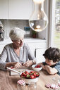 Grandmother sitting at kitchen table, preparing strawberries, grandson sitting beside her, watching - ISF01278