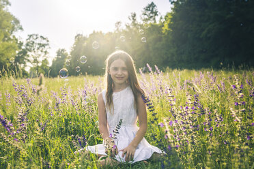Portrait of smiling girl crouching on flower meadow at evening twilight - SARF03742