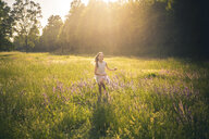 Smiling girl running on flower meadow at evening twilight - SARF03745