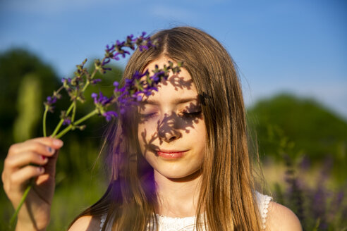 Portrait of girl with purple blossom at evening twilight - SARF03748
