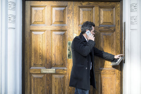 Businessman using smartphone pressing doorbell - CUF04896