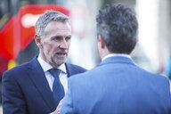Businessmen in street talking, London, UK - CUF04899