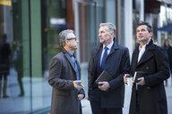 Businessmen talking in street - CUF04905