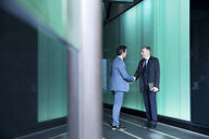 Businessmen shaking hands in modern glass building, London, UK - CUF04911