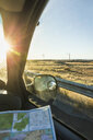 Wing mirror view of man with map on the road in sunlight, Arizona, USA - CUF04920