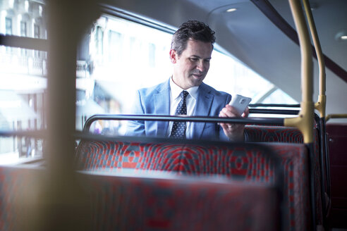 Businessman looking at smartphone on double decker bus - CUF04938