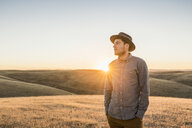 Man looking at rolling prairie hills at sunset, Bakersfield, California, USA - CUF04941