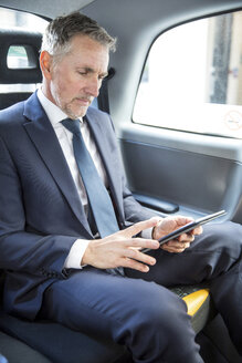 Mature businessman looking at digital tablet in taxi cab - CUF04944