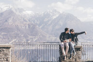 Couple sitting on terrace wall over mountain lakeside, Monte San Primo, Italy - CUF04965