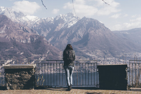 Rear view of woman looking out over lake and mountains, Monte San Primo, Italy - CUF04986