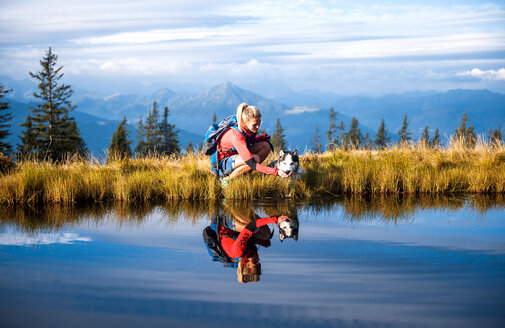 Austria, Salzburg State, female hiker with dog - HHF05566