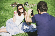 Over shoulder view of man photographing girlfriend sitting in park, Arezzo, Tuscany, Italy - CUF05146