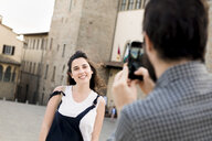 Over shoulder view of man photographing girlfriend by Arezzo Cathedral, Arezzo, Tuscany, Italy - CUF05158