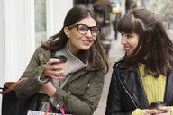 Two young female shoppers chatting while strolling on street  with takeaway coffee - CUF05170