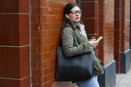 Young woman waiting outside subway station with smartphone - CUF05173