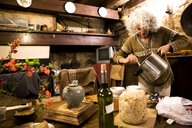 Mature woman serving soup in her rustic french kitchen - CUF05254