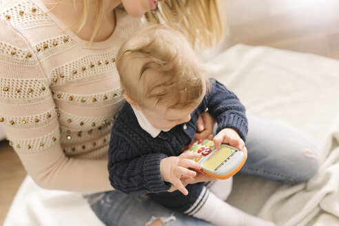 Mother holding baby with toy smartphone - CUF05335