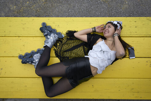 Smiling woman with inline skates lying on yellow table - BEF00046