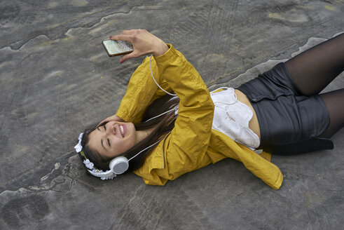 Smiling woman with headphones lying on ground taking selfie with smartphone - BEF00049