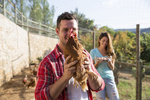Portrait of organic farmer holding free range chicken - CUF05407