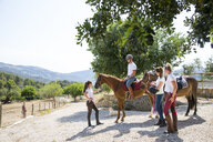 Female groom leading horse rider in paddock at rural stables - CUF05422