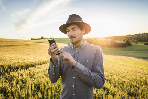 Mid adult man, standing in field, using smartphone, Neulingen, Baden-Württemberg, Germany - CUF05467