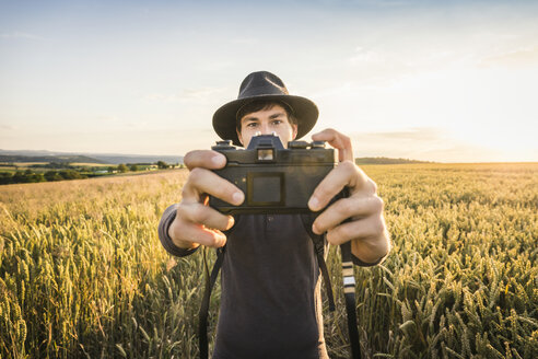 Mid adult man, standing in field, taking selfie with SLR camera, Neulingen, Baden-Württemberg, Germany - CUF05473