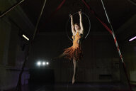 Young female acrobat poised hanging from hoop - CUF05509