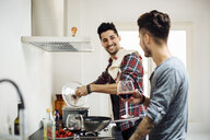 Male couple preparing meal together in kitchen, drinking wine - CUF05554
