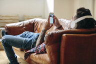 Man relaxing on sofa, wearing headphones, using smartphone - CUF05584
