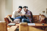 Male couple sitting on sofa, looking at smartphone together - CUF05587
