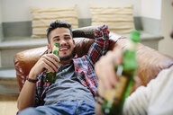 Male couple relaxing on sofa, holding beer bottles, laughing - CUF05590