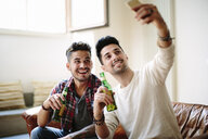 Male couple sitting on sofa, holding beer bottles, taking selfie with smartphone - CUF05593