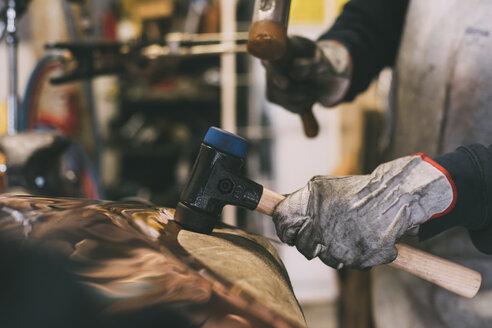 Hands of metalworker hammering copper in forge workshop - CUF05638