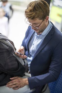Businessman using smartphone in metro - BEF00055