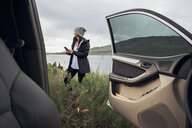 Young woman standing beside Dillon Reservoir, holding smartphone, view through parked car, Silverthorne, Colorado, USA - ISF01339
