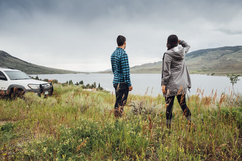 Couple standing beside Dillon Reservoir, looking at view, Silverthorne, Colorado, USA - ISF01342