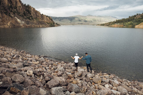 Couple walking on rocks beside Dillon Reservoir, elevated view, Silverthorne, Colorado, USA - ISF01357
