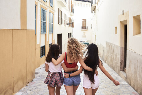 Spain, Mallorca, Palma, rear view of three young women walking in the city embracing each other - IGGF00470
